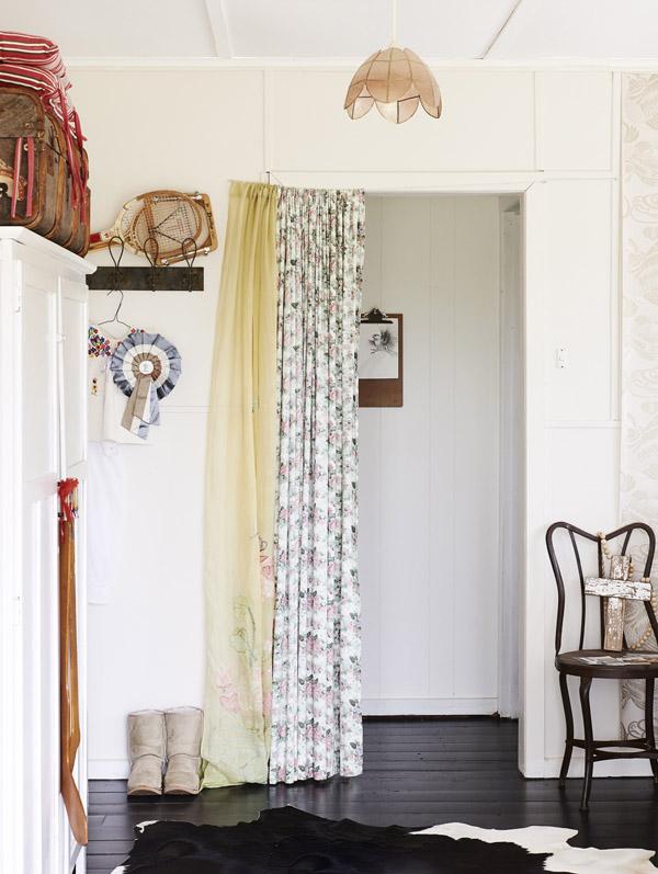 Cadeira Kabinett Vintage e cortina de flores no quarto. Tapete de pele de vaca, alternativa bacana e de bom preço.