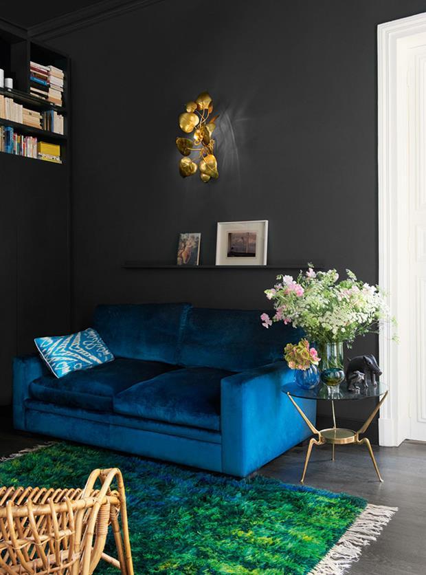 O sofá azul se descola lindamente do fundo escuro.