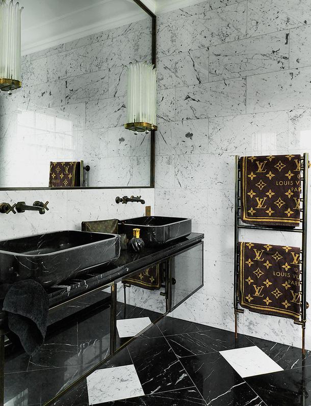 Arandelas anos 1940 são ponto focal no banheiro em mármore preto e branco. Chique.