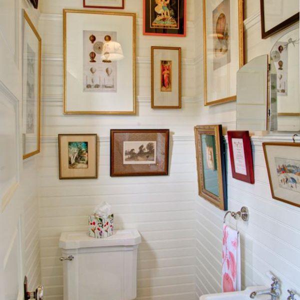 Quadros coloridos e com diferentes molduras dão charme ao banheiro no ato. Uma luminária ou mesmo um spot simples ajuda muito.