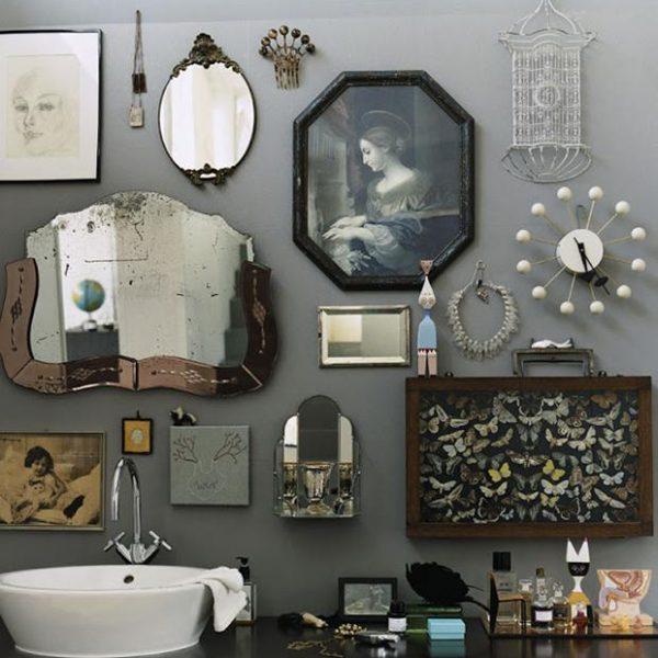Mistura bacana de espelhos, quadros e objetos sobre fundo cinza.