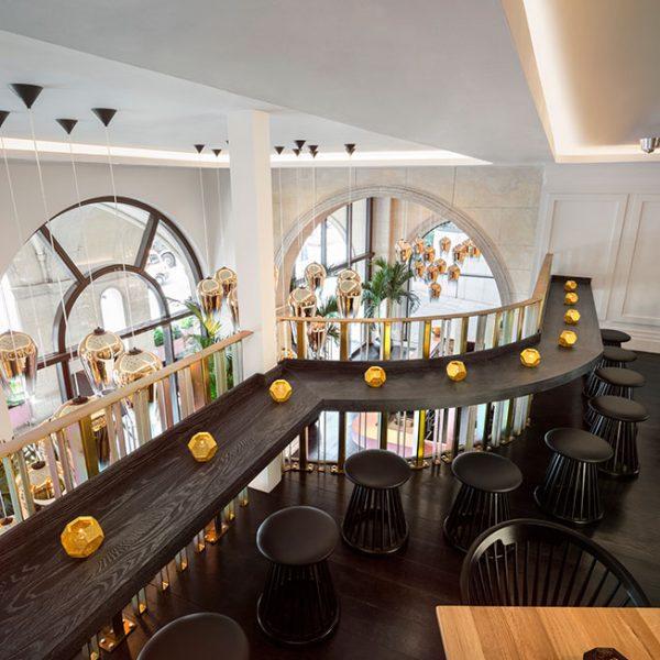 A madeira escura é a base da decoração. O grande balcão percorre o andar superior.