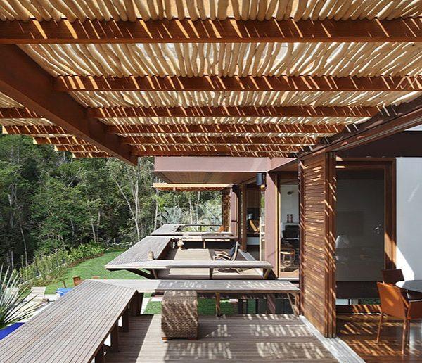 Pergolado que combina estrutura em madeira e tronquinhos irregulares, de Miguel Pinto Guimarães.