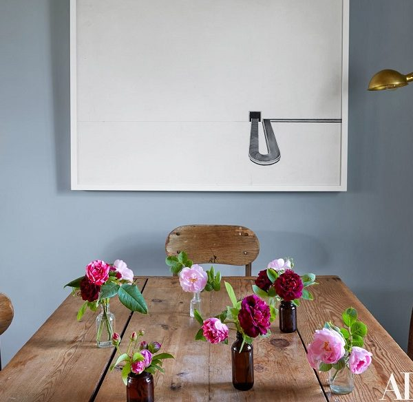 Frascos fazem as vezes de vasos sobre a mesa antiga. A obra é do dono da casa.