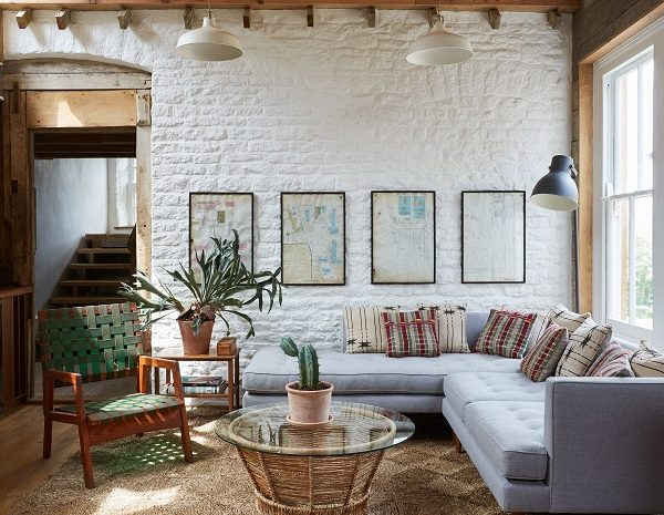 Sofá em L e mobiliário vintage que veio da antiga casa de praia do casal.