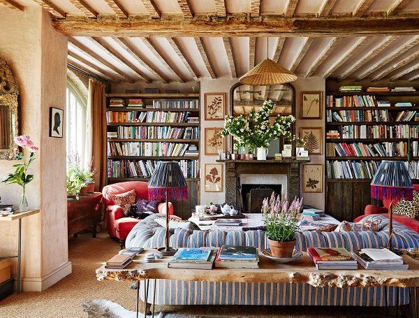 Poltronas vermelhas ladeiam a lareira. Composição animada esquenta o décor inglês.