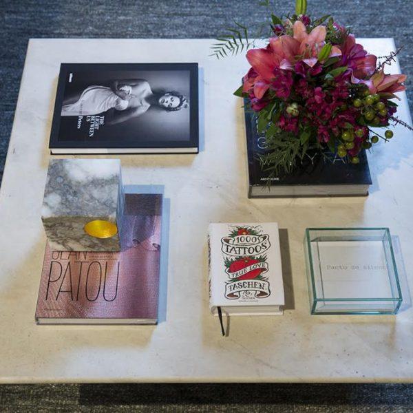 A mesa de centro com tampo em mármore assinada pelo craque Sergio Rodrigues é da Passado Composto, e recebe flores & livros de arte.