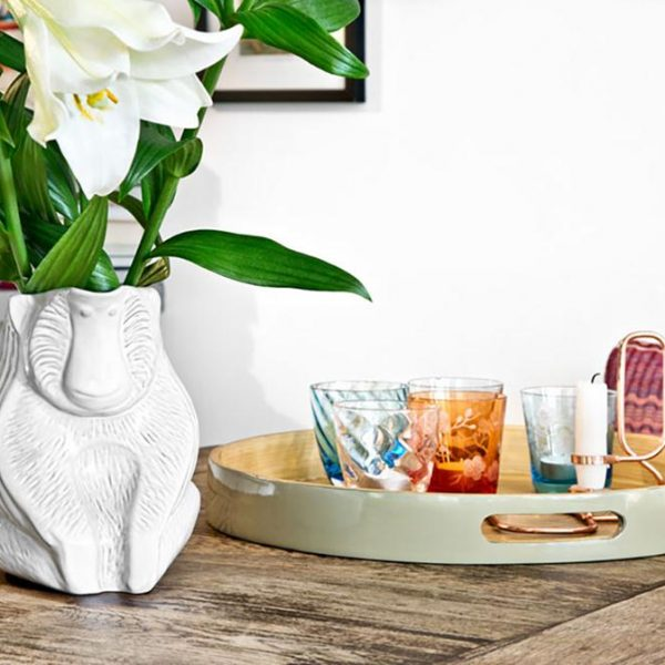 """Vaso """"lindo"""" sobre mesa de jantar."""