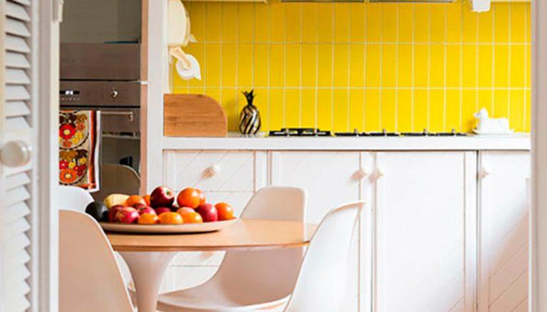 Aqui, o jogo de cores invertido. O amarelo aparece no revestimento, e o branco dos armários e o piso em madeira clara amenizam a intensidade da cor.