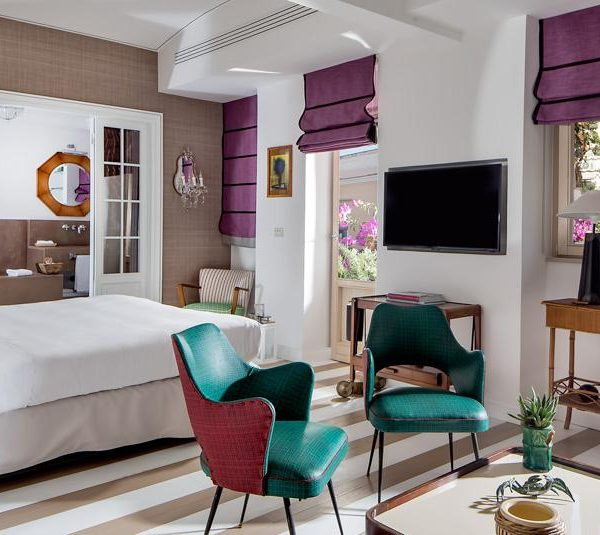 Cores fortes nas poltronas e cortinas alegram o quarto.