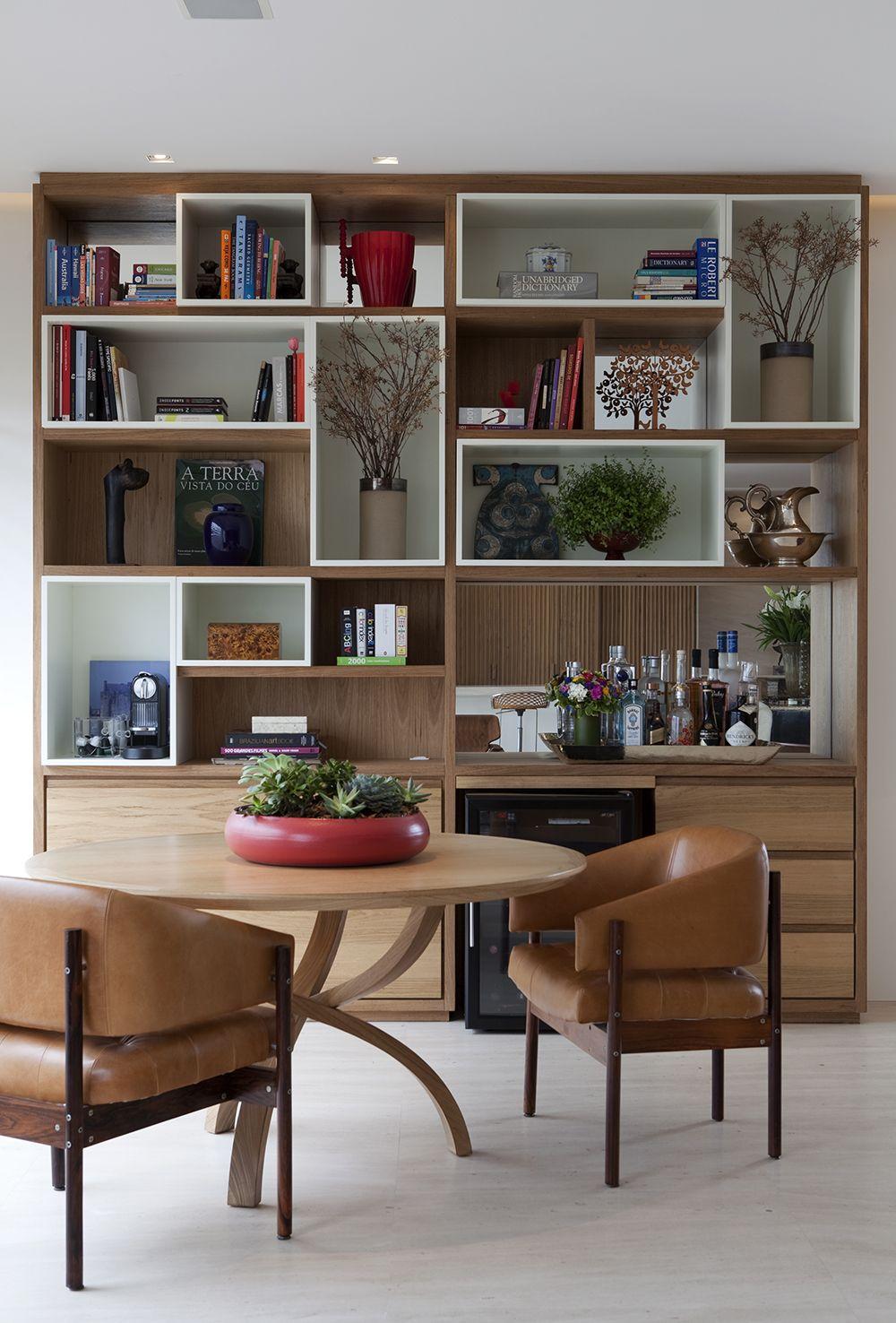 Na sala de jantar mais formal, chique, decorada por Debora Roig, a máquina fica alojada na estante junto à outros utensílios. As cadeiras são de Sergio Rodrigues.