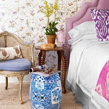 No quarto, cabeceira lilás, garden seat azul e mesa lateral em madeira marchetada.
