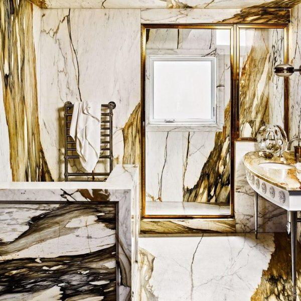 Mármore Calacatta ouro reveste o banheiro da suíte master. Puro drama.