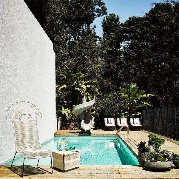 A parede da piscina serve como telão, onde são projetados filmes. Cadeira, linda, e mesa lateral Blackman Cruz.