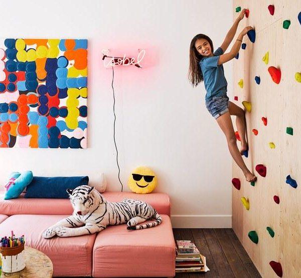 Willow Romanek, com 10 anos, escala a parede de pedra na sala de jogos.