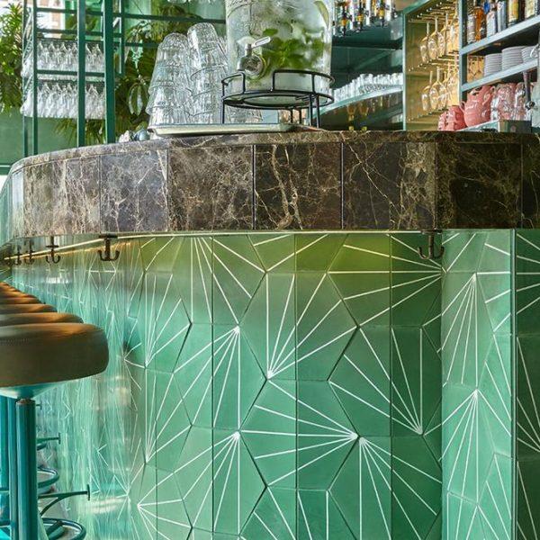 O balcão do bar, em cerâmica verde com grafismos e mármore nobre.