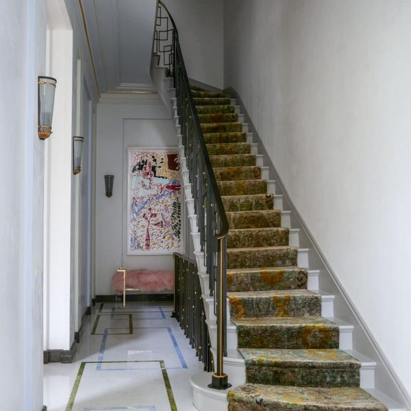 No hall de entrada, o tapete da escada foi feito com seda indiana. Piso de mármore customizado, arandelas de 1947 assinadas por Gilbert Poillerat, e obra de Patrick Heron.