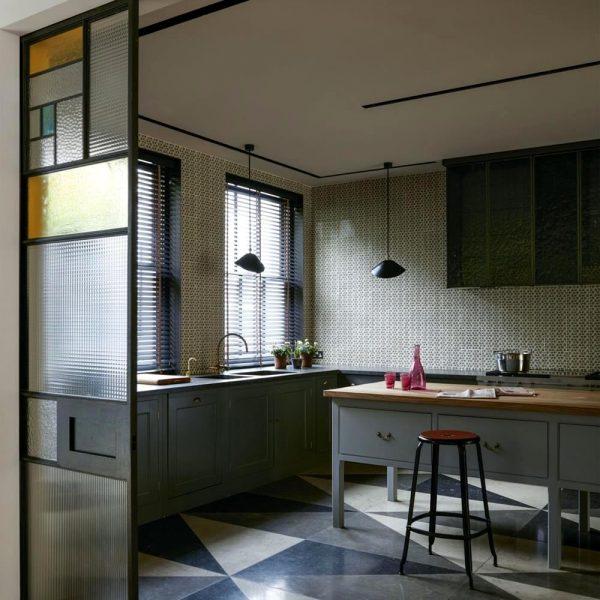 Serge Mouille assina os pendentes da cozinha. Azulejos Neisha Crosland e piso com três tipos de limestone.