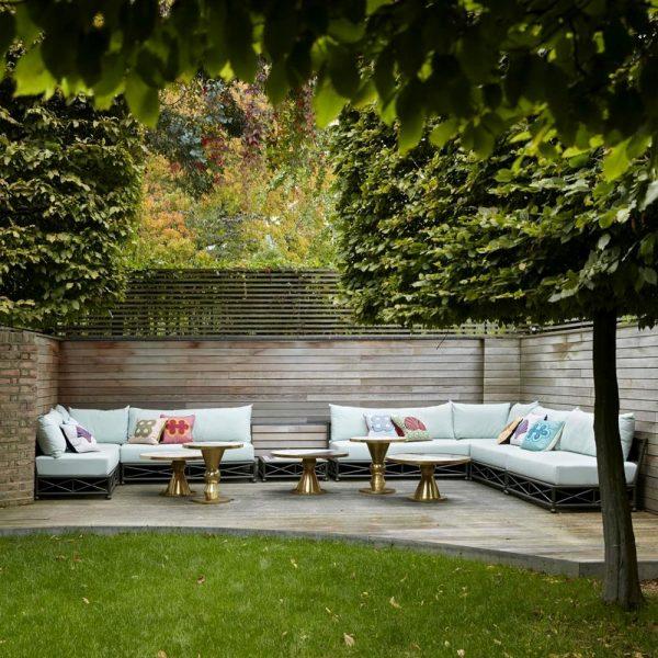 O jardim dos fundos, com sebes de buxo e teixo. Os sofás receberam tecido impermeável e as mesas em latão e mármore foram desenhadas especialmente para o projeto.