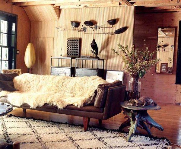 Pele sobre sofá de couro acompanhada por mesa lateral feita de tronco.