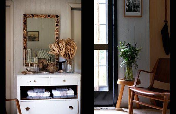 Espelho com moldura de conchas e coral enfeitam a cômoda branca.