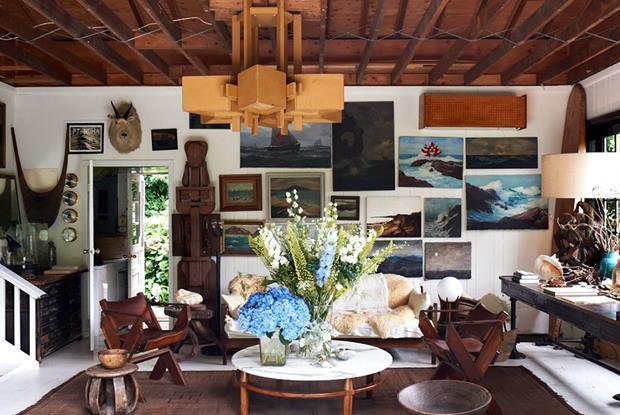 O living conta com mesa de centro do brasileiro Sérgio Rodrigues e sofá com peles. Flores azuis se confundem com as belos trabalhos na paredes. Repare que muitos não receberam moldura, o que combina demais com a decoração despojada.
