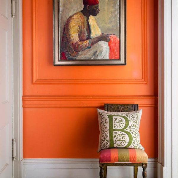 O laranja forte quebra a rigidez das molduras no hall de entrada. Piso em mosaico e cadeira antiga. A obra na parede foi garimpada em mercado de pulgas.