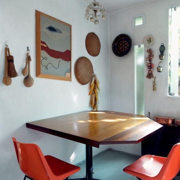 O indígena e o caiçara convivem com piso em pastilhas azuis, cadeiras de plástico laranja, mesa em madeira e pendente antigo em cristal.