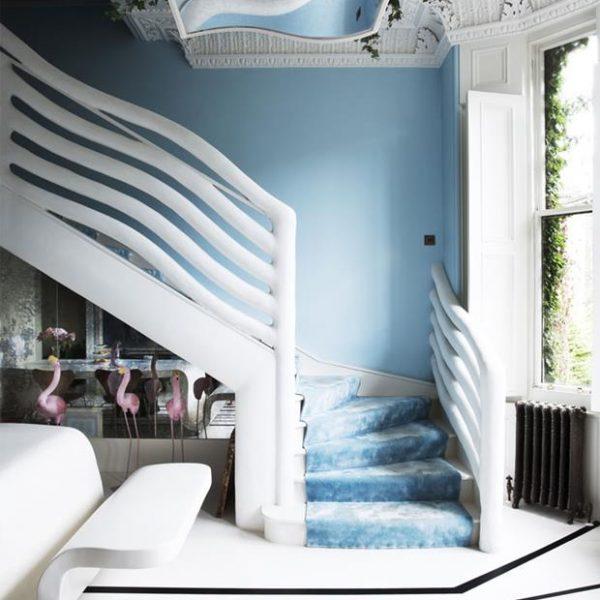 Sob a escada, flamingos. Guarda corpo em linhas ondulantes e luminária com plantas. Inventivo.