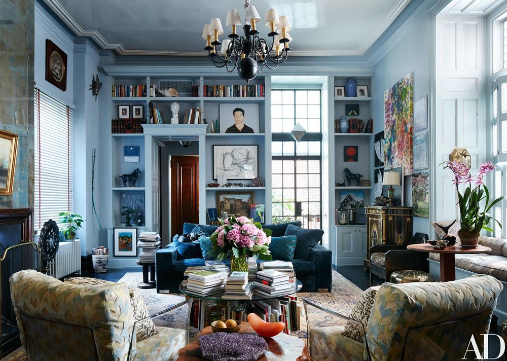 O living chiquérrimo em estilo eternamente identificado como novaiorquino, recebeu paredes e estantes em azul com toque cinza, muitas obras de arte, livros e objetos queridos.