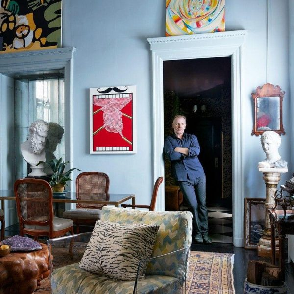 "Pierson faz pose no vão da porta de estilo neoclássico. Poltrona em acrílico da Kartell e mesa lateral ""Walnut"", de Alma Allen."