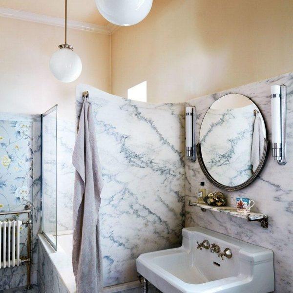 """Papel de parede Zoffany complementa a decoração do banheiro, que recebeu mármore """"Montclair Arabesco"""". Luminárias e acessórios vintage."""