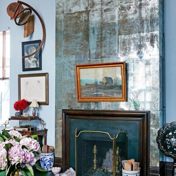 Painel espelhado antigo e acessórios do século XIX dão up certeiro na lareira que já existia no apartamento.