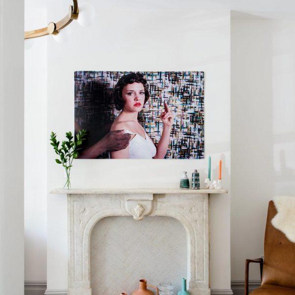 Uma lareira de mármore original agora atua como uma área de exibição para a coleção colorida de vasos de CB2. O tapete floral assinado por Madeline Weinrib acrescenta um toque de estampa para o living.