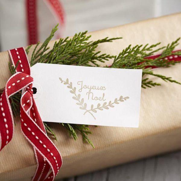 A fitinha diferente e o cartão feito à mão sobre papel craft ficam lindos quando acompanhados de um pedacinho de pinheiro.