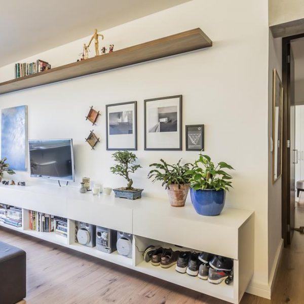 O móvel desenhado pelo arquiteto acomoda os livros, objetos e sapatos da dupla de moradores.