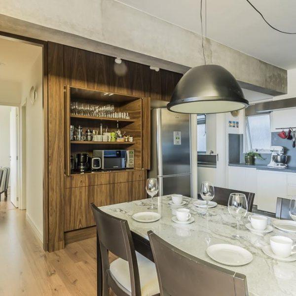 A porta para a área intima, assim como o armário que guarda parte da louça e equipamentos para o café, estão camuflados no painel.