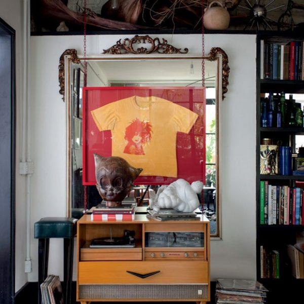 Radiovitrola, herança de família, camiseta vintage da cantora inglesa Siouxsie Sioux, emoldurada por Paulo, e banqueta dos anos 1960.