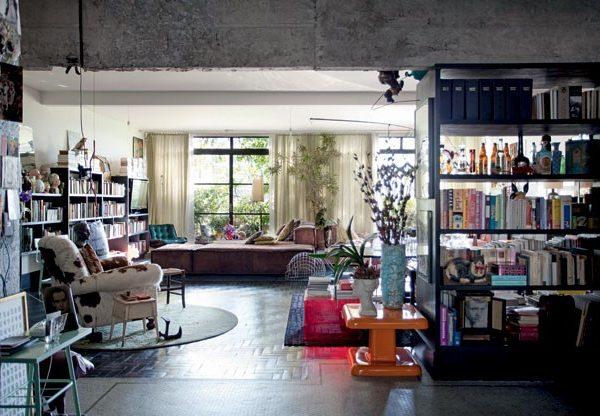 """No living, parte dos livros de Paulo e a junção de pisos diferentes, remanescentes da reforma; junto à janela, ao fundo, se vê o sofá do Estudiobola, a tradução perfeita para uma """"cama"""" na sala, desejo de Paulo."""