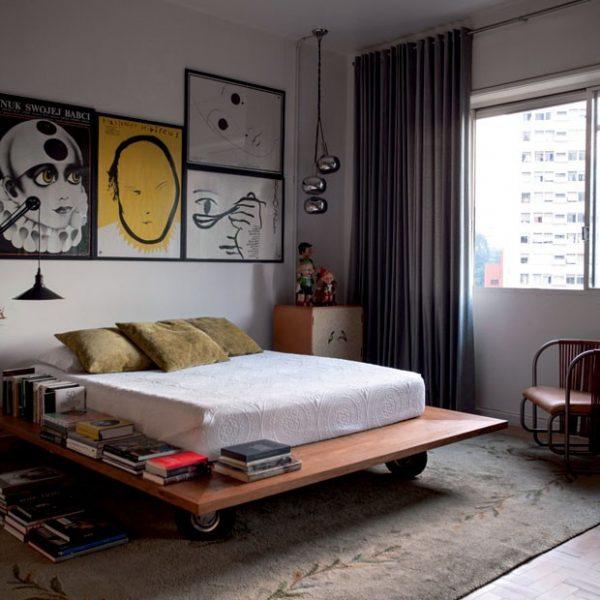 No quarto, cama desenhada por Aldi, tapete Santa Helena, luminária dos anos 1960 e na parede, antigos cartazes poloneses.