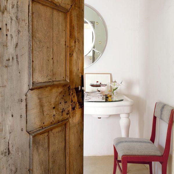 Lavabo com louça em porcelana, espelho do estúdio de Isabel e cadeira vintage.