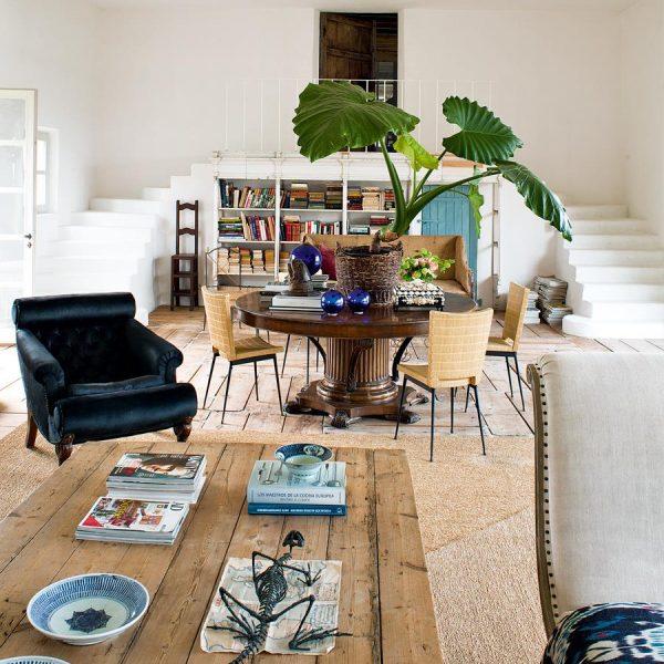 Ao lado da escada, pequeno estar com biblioteca. Ao centro, mesa inglesa de nogueira.