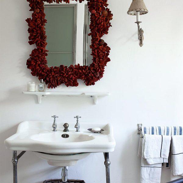 O banheiro da piscina com pia antiga e espelho em coral.