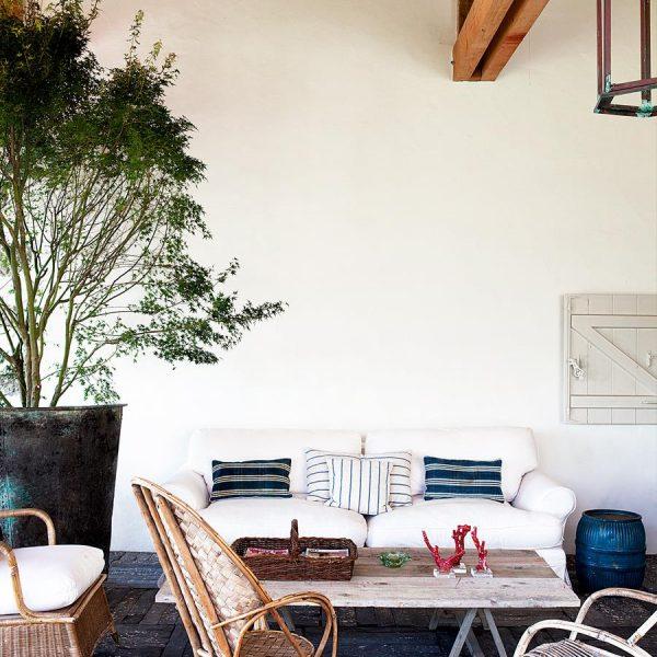 Na varanda, a grande jabuticabeira traz o verde para mais perto da vista. Cadeiras francesas anos 1950 e sofá revestido de sarja branca.