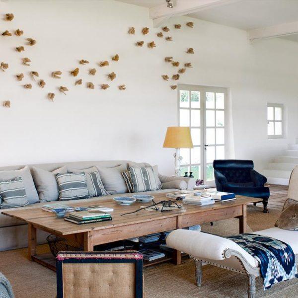 """No living, sofá de mais de quatro metros, bem de acordo com o espaço, chaise francesa com tecido Ikat, e na parede, obra """"Migración"""", instalação de Gloria García Lorca."""