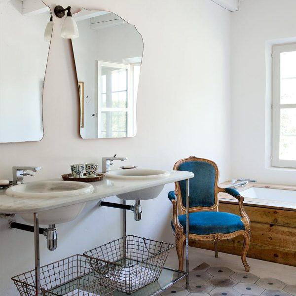 No banheiro dos hóspedes, pia dupla sobre mármore branco, espelhos de mercado de pulgas e cadeira francesa antiga herdada.