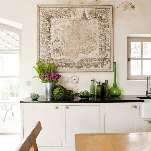 Na cozinha, antigo mapa da França faz companhia a garrafas e cerâmicas compradas nas redondezas.