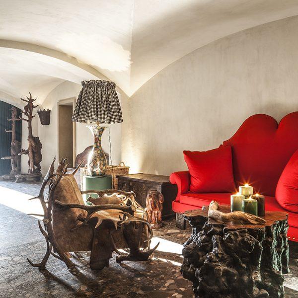 A entrada, enorme, foi concebida como uma sala de estar. Surpreendentemente inserido na decoração, o sofá vermelho inglês do século XIX, que evoca os lábios de Mae West, faz companhia à cadeira de chifre de fabricação tradicional da Baviera e mesa de centro de raiz de árvore