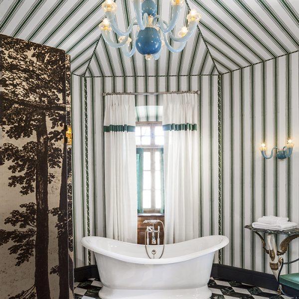 A sala de banho inspirada em Joséphine de Beauharnais, primeira mulher de Napoleão Bonaparte, é toda revestida em tecido listrado e tem pendente e arandela Gio Ponti