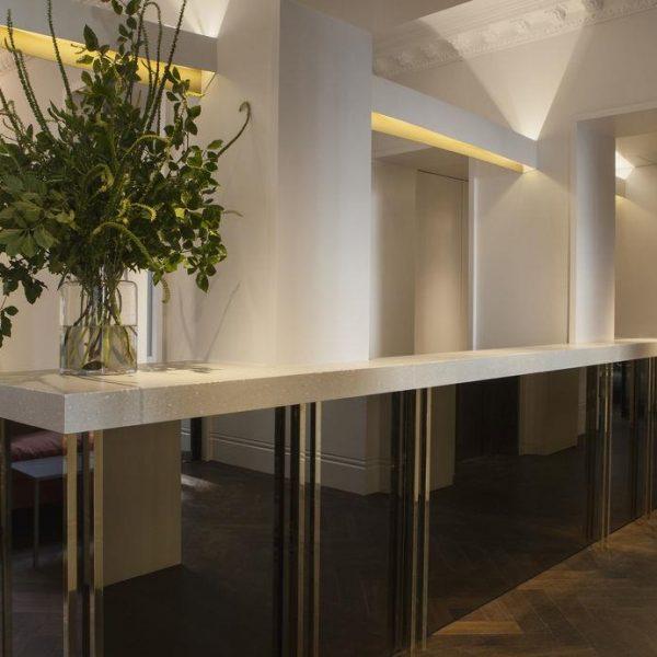 A recepção do hotel inglês recebe balcão de linhas puras e arranjo verde